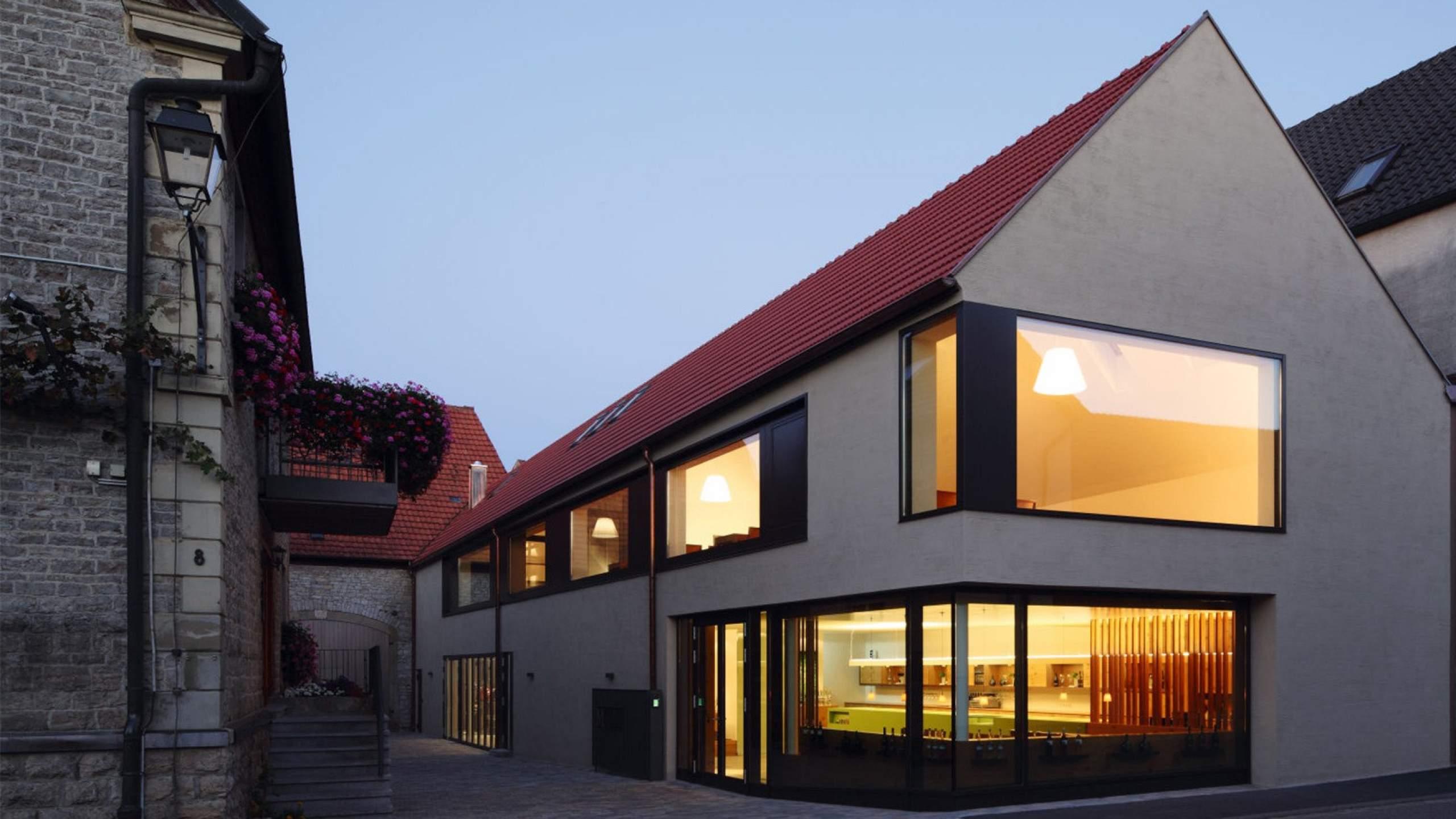 Zimmererarbeiten Gebäude mit Glasfront am Abend beleuchtet